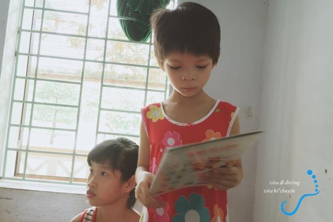 Vân Anh mặc dù chưa biết đọc nhưng vẫn giành một cuốn để xem tranh
