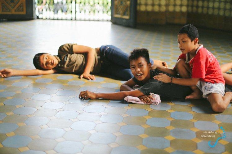 Bọn trẻ nằm nghỉ và đùa nghich ngoài hiên đền thờ.